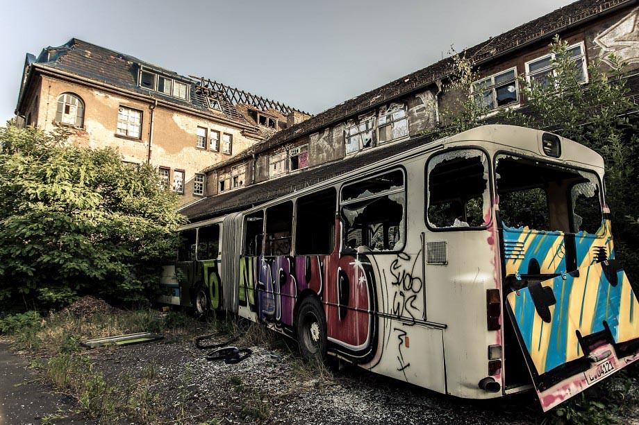 """Ein verlassenes Fabrikgelände in Leipzig samt Bus in verfallenem Zustand. Ein im Weitwinkel aufgenommenes Foto - es ist viel auf dem Bild zu sehen, wirkt jedoch nicht überfrachtet, da ein inhaltlich sinnvoller Bezug zwischen Hauptmotiv (Bus) und """"Hintergrund"""" (verlassenens Fabrikgelände) hergestellt wird."""
